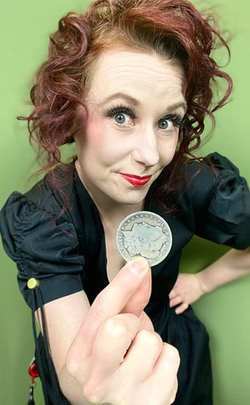 Female magician holds up a coin